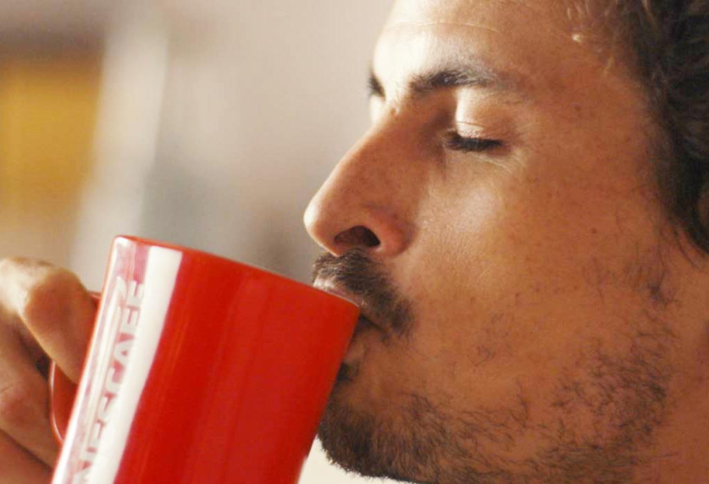 Hombre bebiendo NESCAFÉ Classic de una taza NESCAFÉ roja
