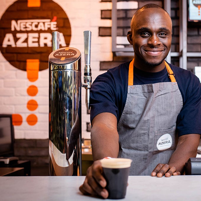 A man serving a coffee over a counter