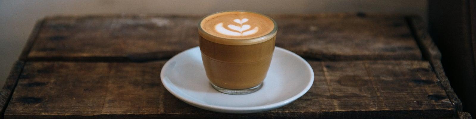 A cortado coffee in a glass