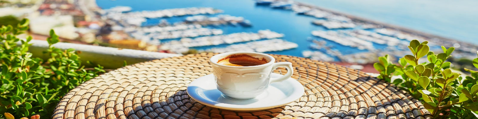 A cup of Italian coffee on a table overlooking a marina