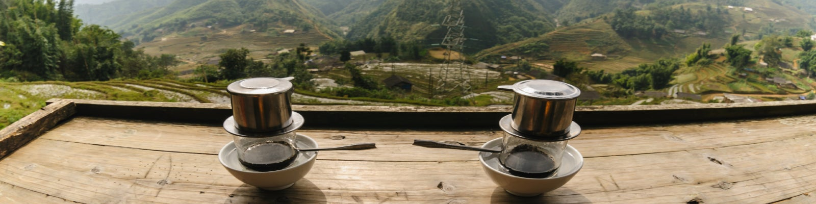 Two Vietnamese coffees on a table overlooking a valley